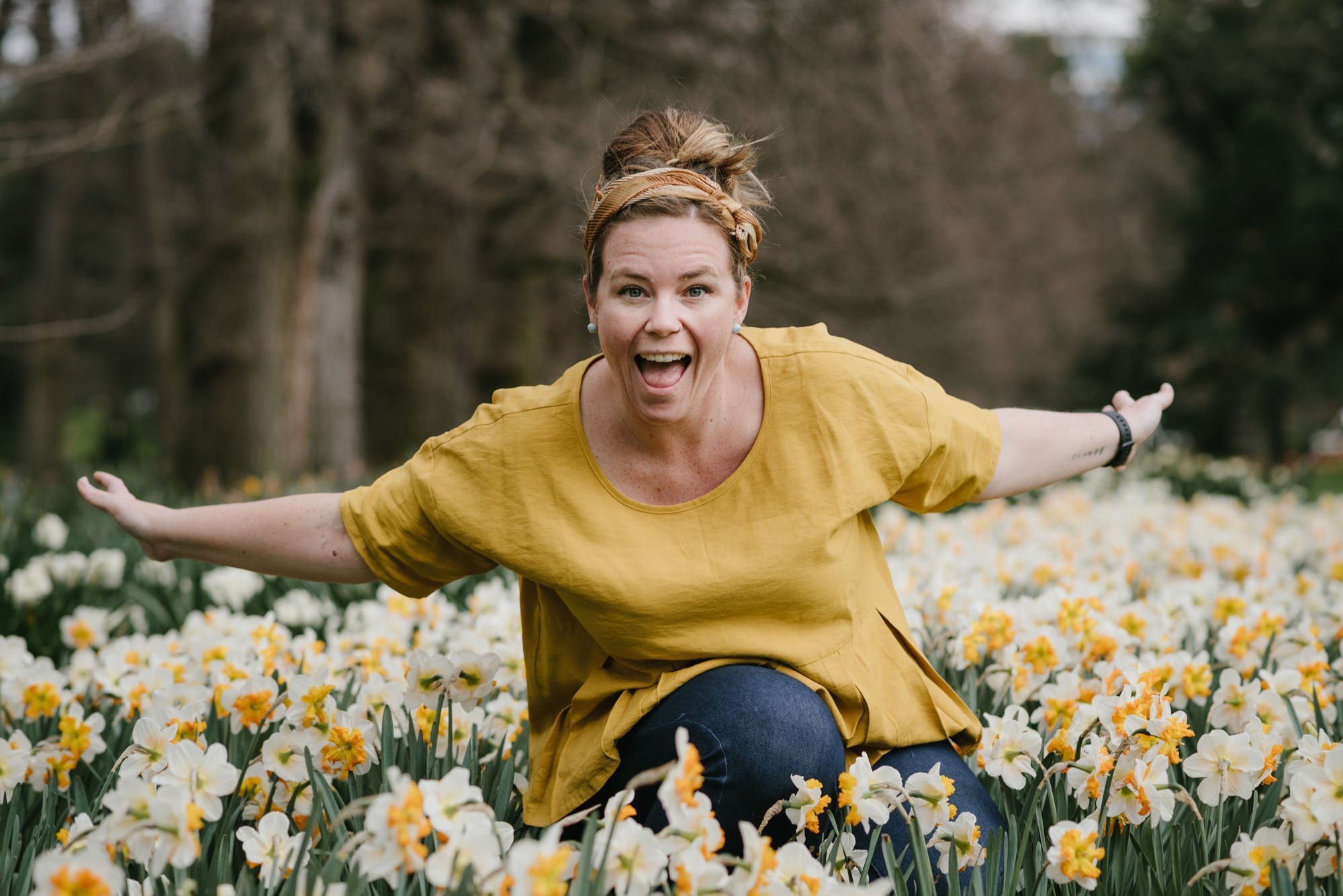 Marion Piper wearing a gold top and blue jeans with her arms outstretched crouching in a field of flowers.