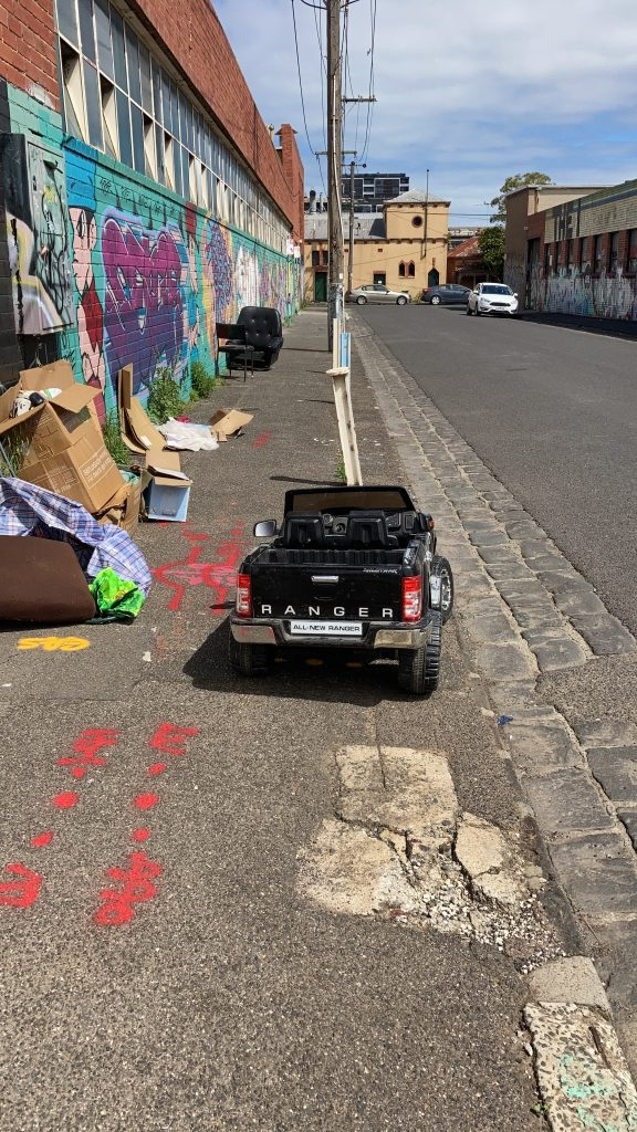 A kid's ranger toy car parked on the footpath on Ovens St, Brunswick.