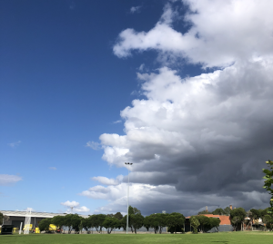 A storm rolling in over a sports oval in Brunswick, Victoria. Half the sky is blue, half the sky is storm clouds.