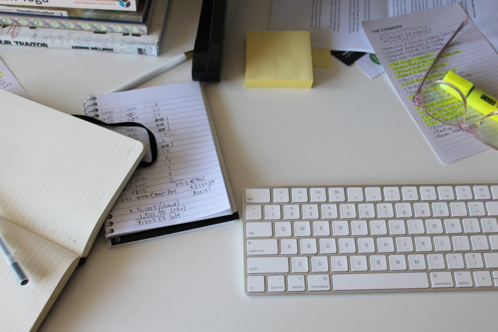 The top of a white desk with a white keyboard, notebooks, highlighter and pen.
