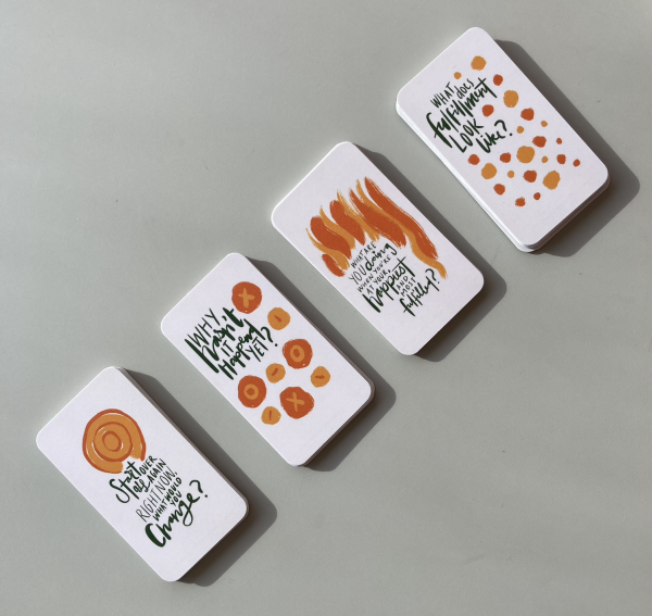 Four piles of The Expression Deck Cards in a row on a green table.