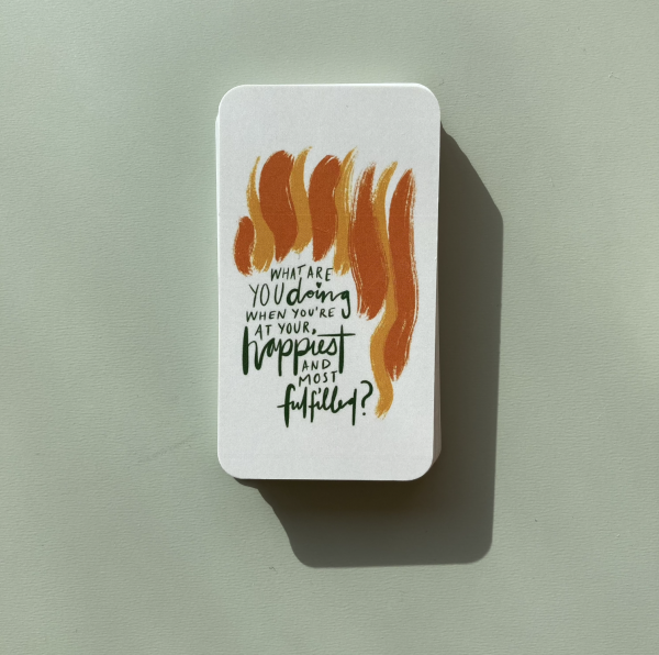 """One neat pile of The Expression Deck cards on a green table with the top card turned over that reads: """"What are you doing when you're at your happiest and most fulfilled?""""."""