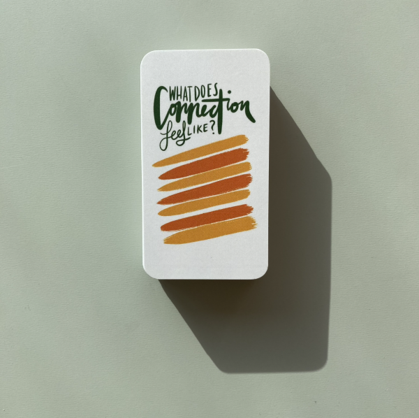 """One neat pile of The Expression Deck cards on a green table with the top card turned over that reads: """"What does connection feel like?"""""""