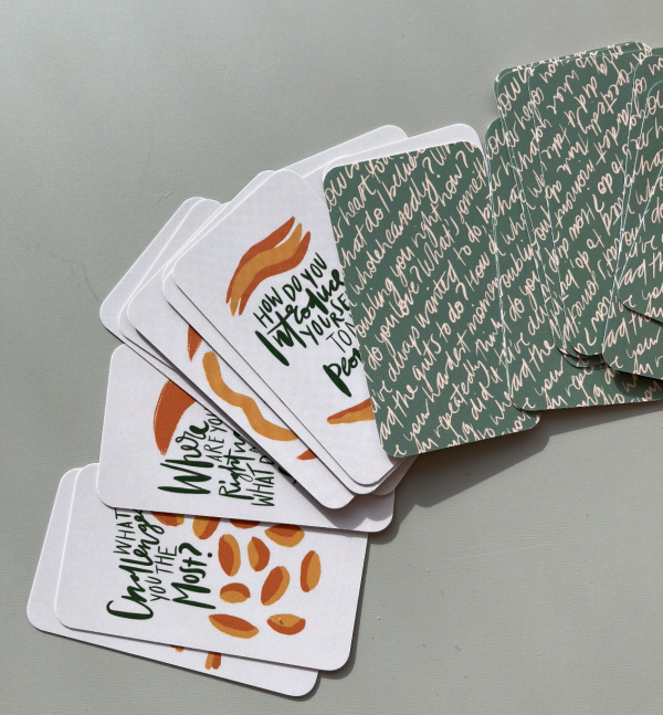 The Expression Deck cards fanned out –half turned question side up, half face down –on a green table.