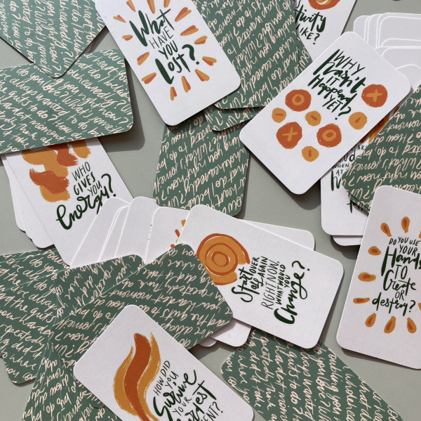 The Expression Deck cards scattered in a pile on a table, some are face up, others are face down.